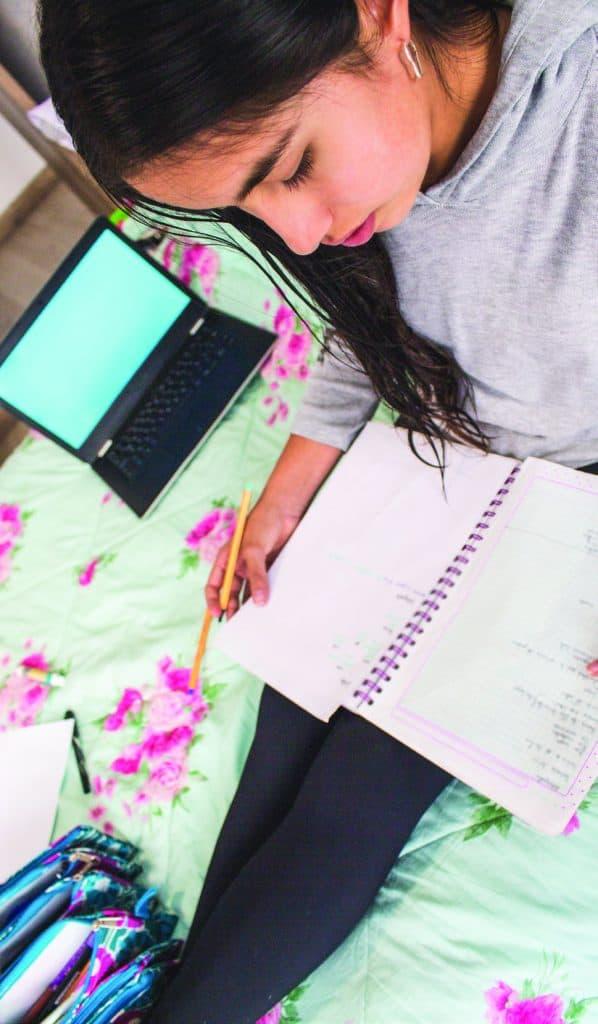 Girl studies in her notebook in bed